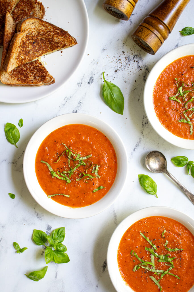 Overhead view of three bowls of roasted red pepper and tomato soup surrounded and garnished by fresh basil leaves.