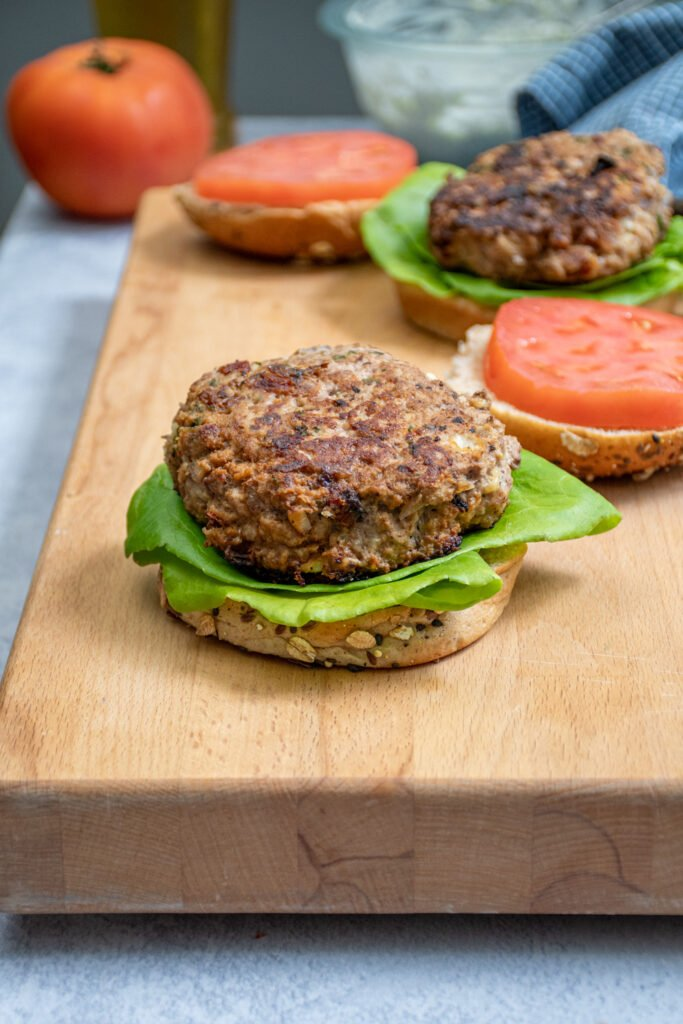 A greek turkey burger on a bun sit-in non a butcher block.