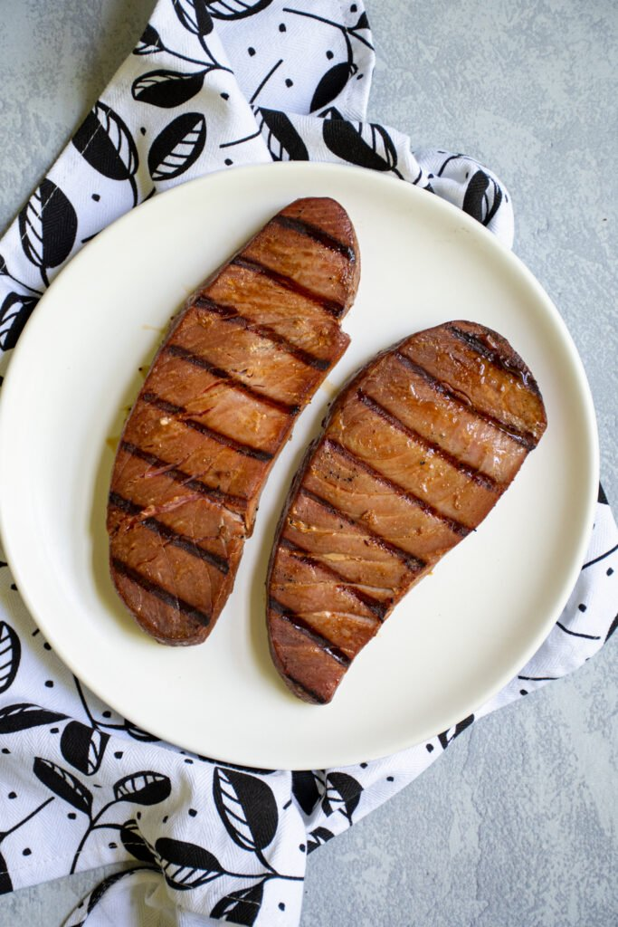 Grilled tuna steaks sitting on a white plate.