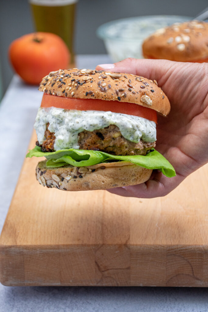 A hand holding up a Mediterranean Turkey burger with Tzatziki sauce dripping off the side.