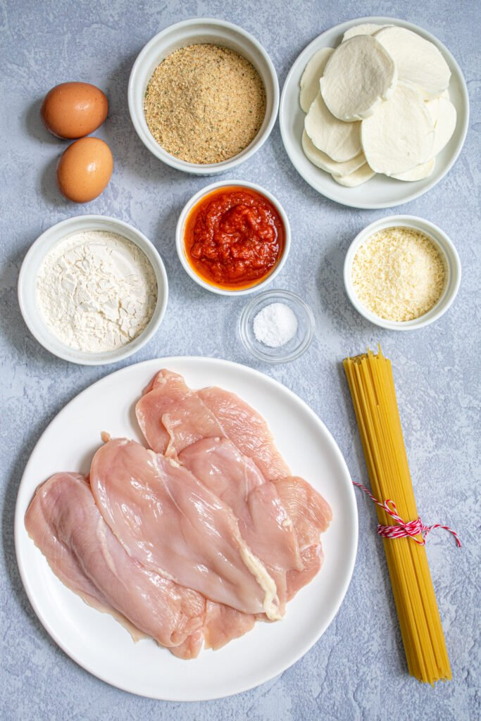 Ingredients need to make Baked Chicken Parmesan laid out on a tabletop.