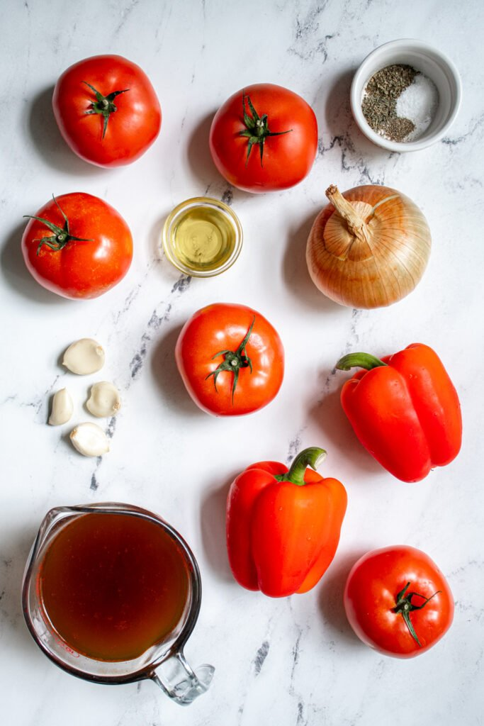 All the ingredients needed to make roasted red pepper and tomato soup laying flat on a countertop.