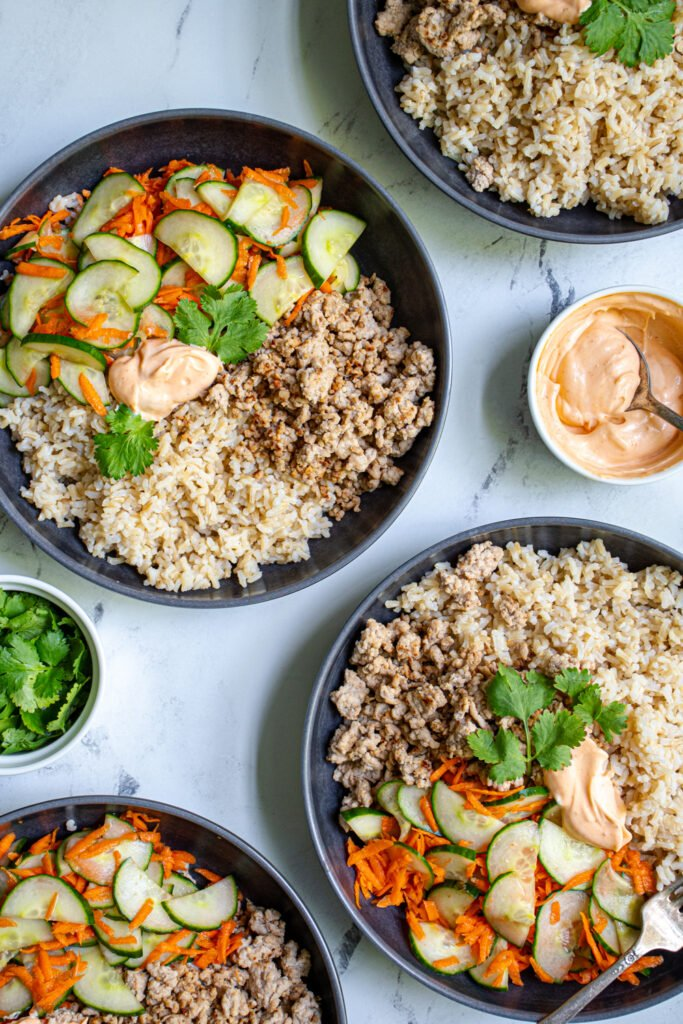 Photo of four bowls filled with brown rice, ground pork, and quick pickled vegetables.