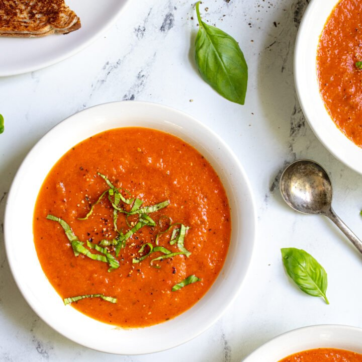 Close up of three bowls of tomato and red pepper soup on a countertop with basil leaves and spoon.