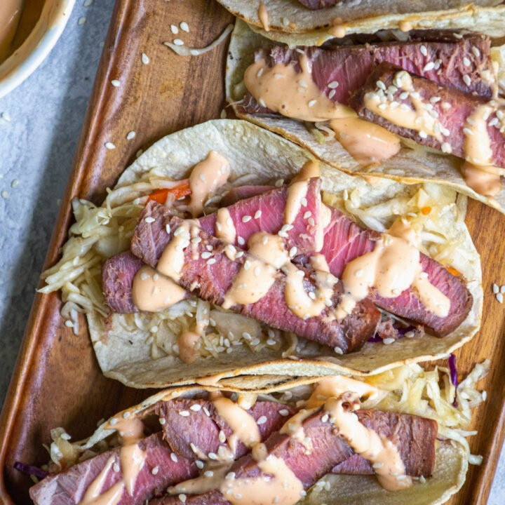 Overhead view of four seared tuna tacos on a wooden serving board garnished with sriracha mayo and sesame seeds.