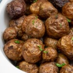 Pinterest pin with text 'Air Fryer Baby Potatoes', image showing a white serving dish filled with salty baby potatoes.