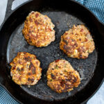 Pinterest Pin with text 'Mediterranean Turkey Burgers' image of a black skillet with four just cooked turkey burgers.