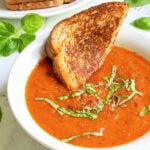 Pinterest Pin with text 'Roasted Red Pepper & Tomato Soup, easy and healthy, made with fresh veggies' image showing a white bowl of tomato soup with a slice of grilled cheese.