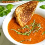 Pinterest Pin with text 'easy and healthy Roasted Red Pepper & Tomato Soup' image of a white bowl of tomato soup with basil leaves.