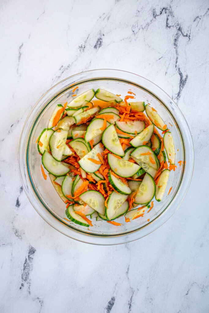 A bowl containing the quick picked veggies, carrots and cucumbers in rice vinegar.