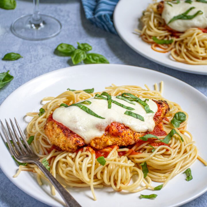 White plate piled high with pasta topped with an Oven Baked Chicken Parmesan covered in melted cheese and fresh basil garnish.