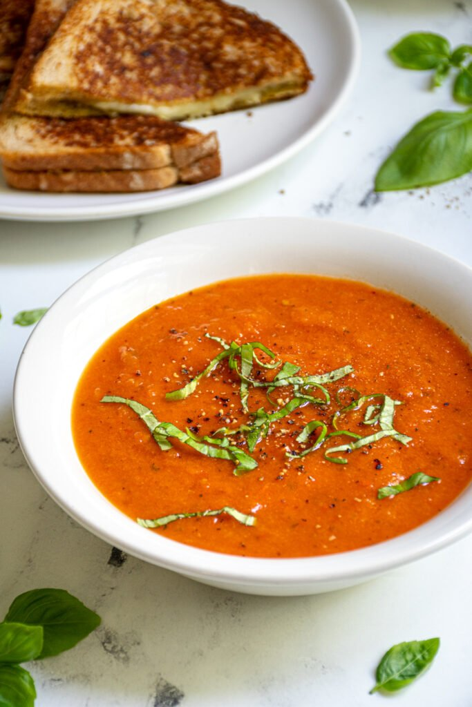 White bowl filled with roasted red pepper and tomato soup topped with freshly cracked black pepper and fresh basil leaves sitting next to a plate of grilled cheese.