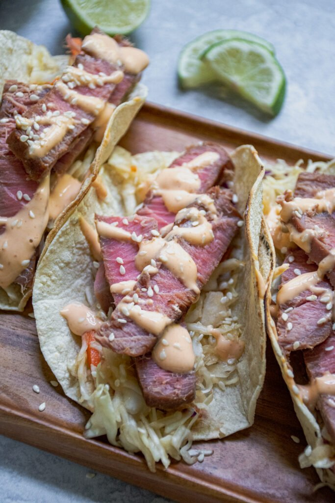 A side view of a close up of a tuna steak taco showing of slice tuna with pink middle garnished with sriracha mayo and sesame seeds.
