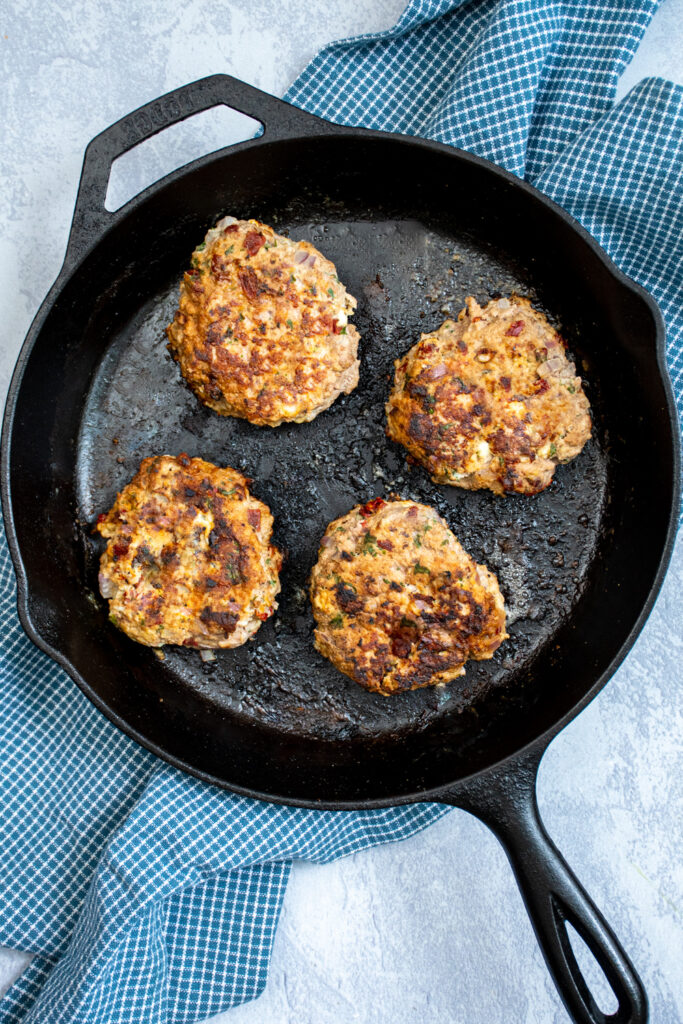 Skillet with 4 greek turkey burgers just cooked.