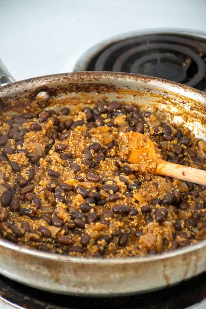 A skillet with cooked black beans and quinoa to be used as a flavorful taco meat.