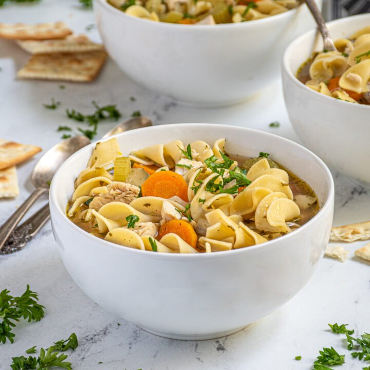 A centered white bowl showing off a large portion of easy to make stovetop chicken noodle soup garnished with fresh parsley and served with saltine crackers on the side.