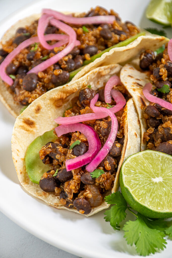 close up of black bean quinoa taco meat in a corn tortilla showing the saucy quinoa and black beans.