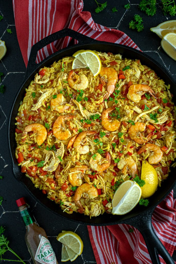 Close up of a pan filled with yellow chicken and shrimp paella with shrimp sitting on top with chunks of chicken, tomatoes, and bell peppers.