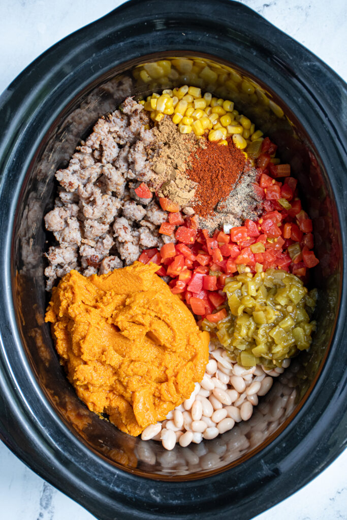 A black crockpot filled with the ingredients to make pumpkin chili, including maple sausage, white, beans, pumpkin, and tomatoes.
