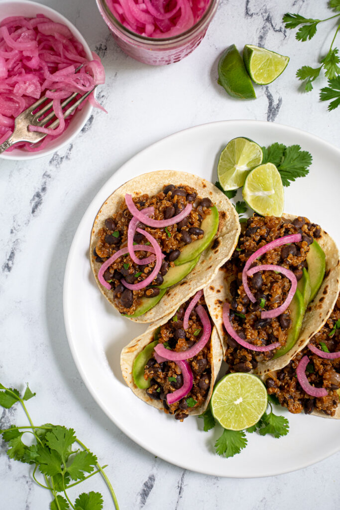 Overhead view of a white plate filled with black bean quinoa tacos garnished with cilantro, pickled onions, and avocado.
