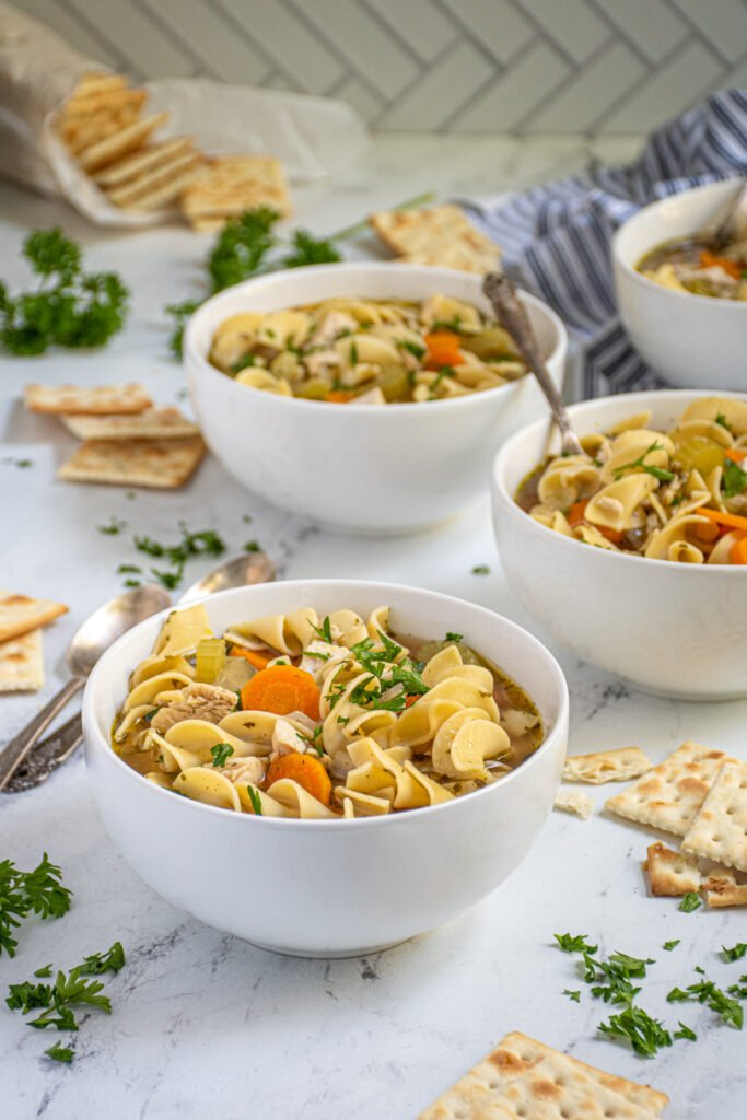 Countertop with four white bowls of easy chicken noodle soup showing off chewy egg noodles, big chunks of chicken, and vegetables garnished with fresh parsley.
