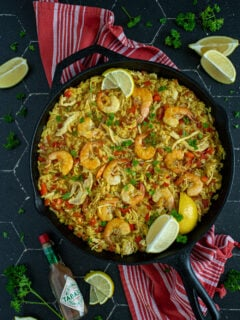 Overhead view of a black pan full of chicken and shrimp paella showing off yellow rice, chicken, red bell pepper, and cooked shrimp garnished with fresh parsley and lemon wedges.