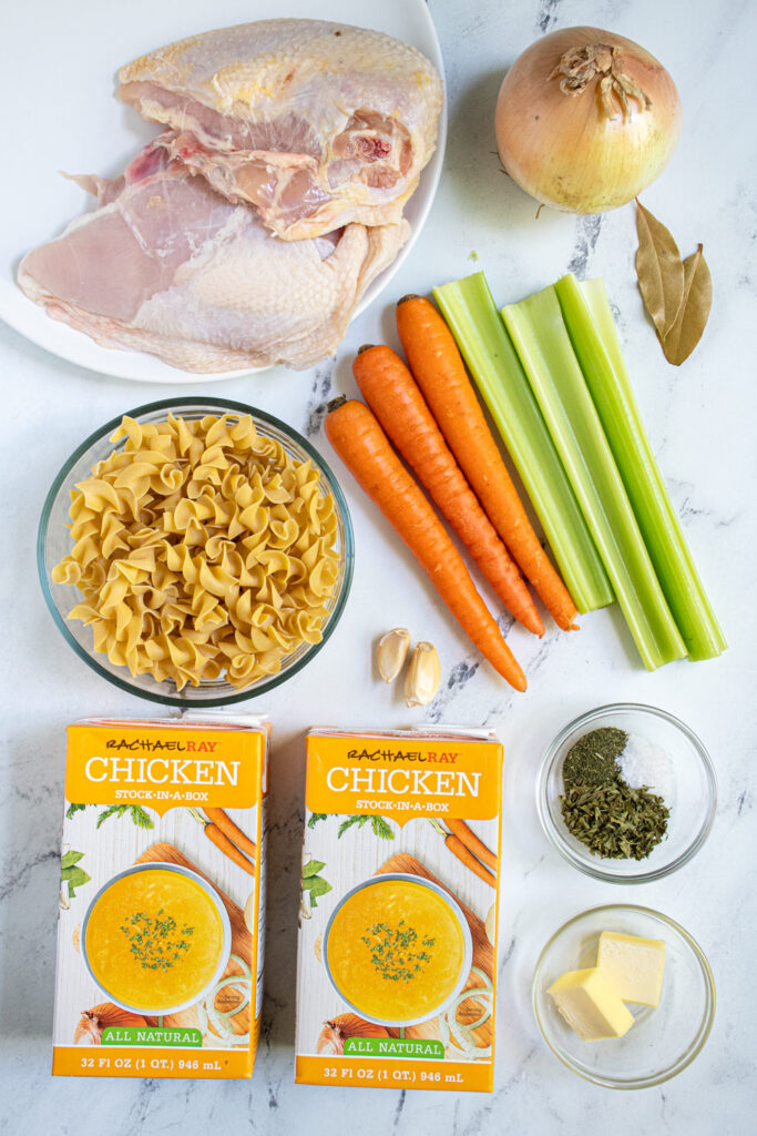 Ingredients needed to make easy chicken noodle soup including split chicken breasts, veggies, and egg noodles.