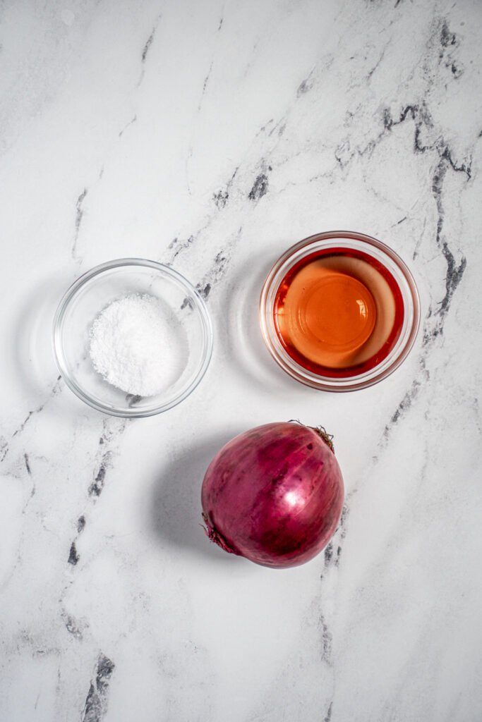 Ingredients for making quick pickled onions including a red onion, salt, and red wine vinegar.