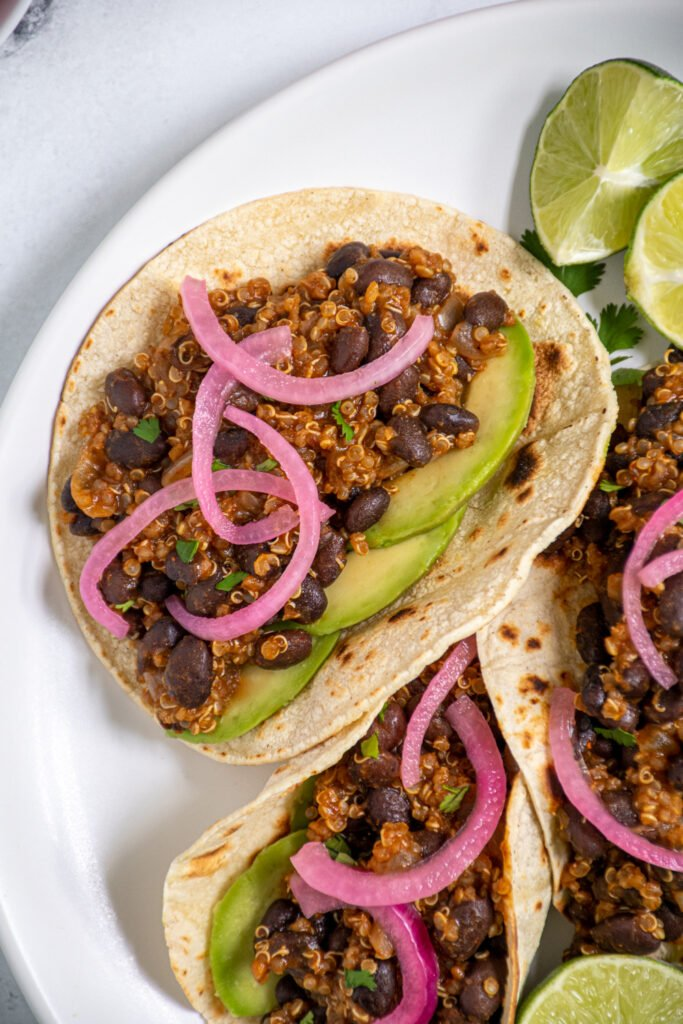 Overhead view of a close up of a corn tortilla filled with black bean quinoa taco meat garnished with cilantro, pickled red onions, and avocado.