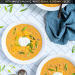Pinterest Pin with text 'Crockpot Creamy Pumpkin Chili', image of bowls of yellow pumpkin chili topped with green onions, and sour cream.