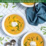 Pinterest Pin with text 'Slow Cooker Pumpkin Chili', image of bowls of yellow pumpkin chili topped with green onions, and sour cream.