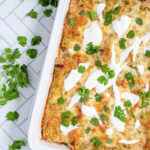 Pinterest Pin with text 'Green Chicken Enchiladas', image of white baking dish filled with green enchiladas.