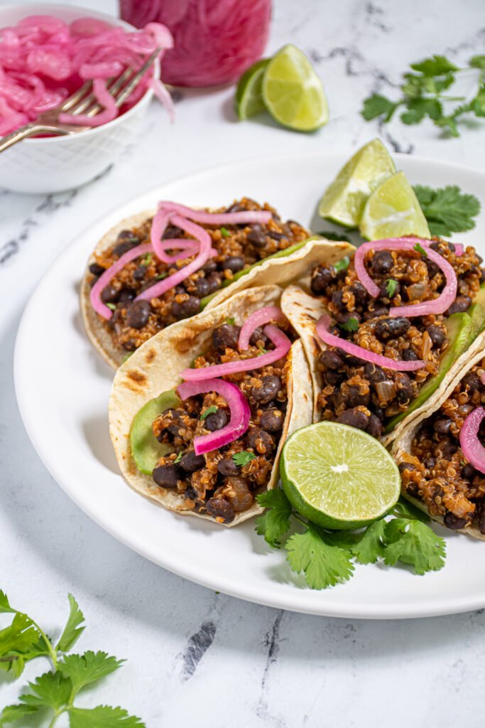 Plate with a bunch of black bean quinoa tacos in corn tortillas topped with pickled onions and avocado.