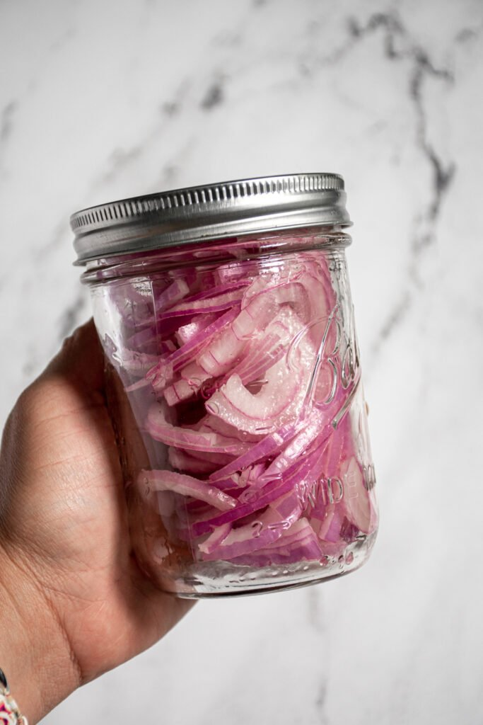 A hand shaking a jar of quick pickled red onions.