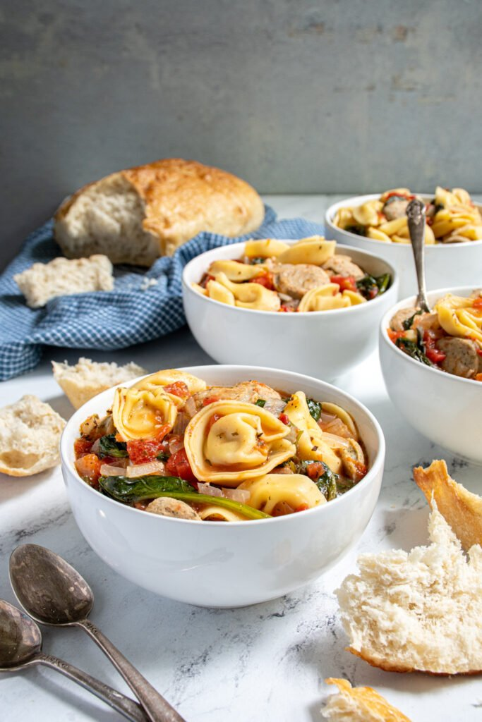 Tabletop with bowls of tortellini soup with chicken sausage and spinach surrounded by bread and spoons.