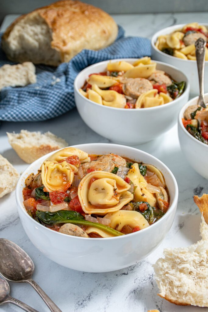 White bowl with chicken sausage tortellini soup with tomatoes and spinach.