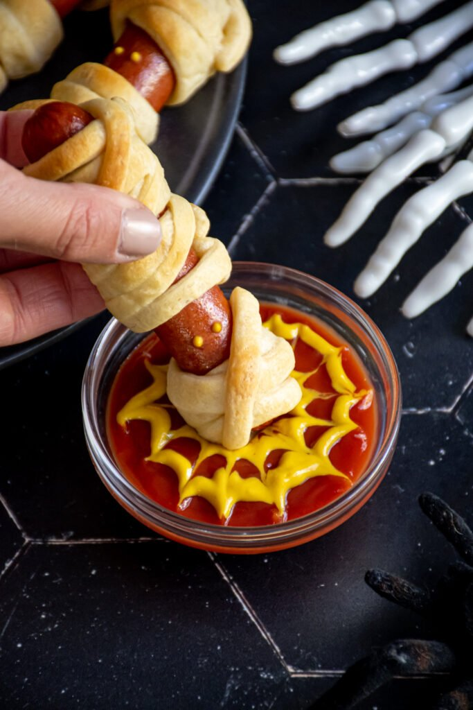A mummy dog being dunked into a cup of ketchup and mustard that is in the design of a spider web.