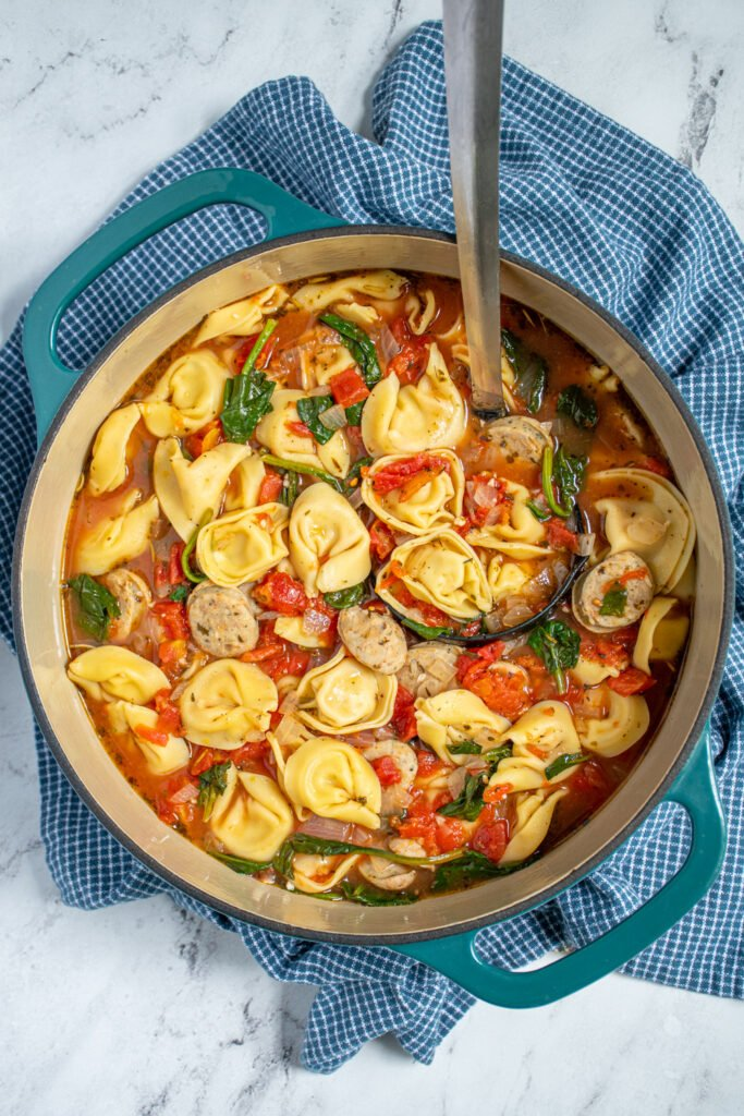 Overhead view of a large teal dutch oven full of chicken sausage tortellini soup with tomatoes and spinach.
