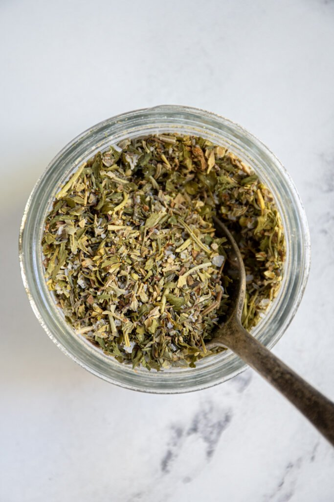 A close up of a jar with a spoon inside with homemade Italian seasoning.