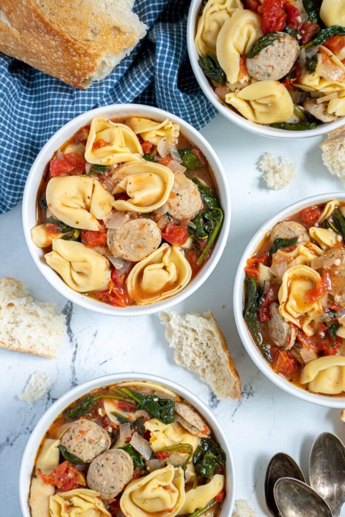 Overhead view of a few white bowls of chicken sausage tortellini soup with spinach and diced tomatoes.