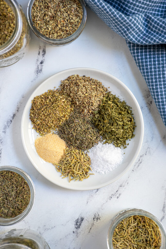 Overhead view of the seven herbs and spices that make up homemade Italian seasoning on a plate.