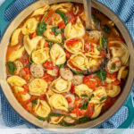 """Pinterest Pin with text """"Tortellini Soup with Chicken Sausage"""", image of a pot of tortellini soup."""