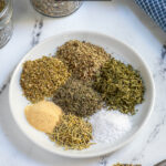 Pinterest Pin with text 'Homemade Italian Seasoning',image of a small plate with Italian seasoning ingredients.