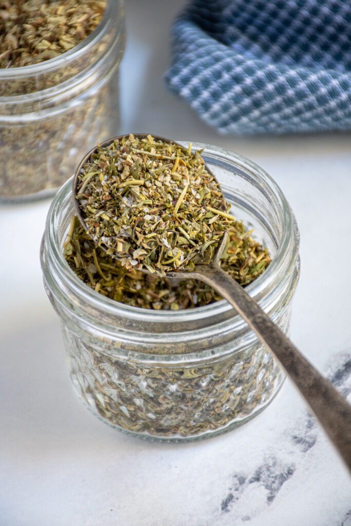 A jar and spoon full of homemade Italian spice blend.